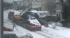 雪で登れないトレーラーを助ける荷台のショベルカー