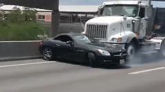横向きになったベンツ SLKを押したまま走る大型トラック
